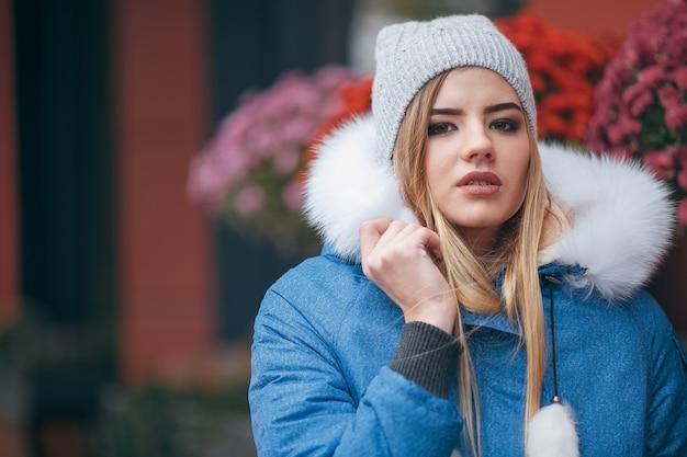 Zakochana w naturze dziewczyna w kurtce spaceruje po jesiennym parku ciepłe ubranie na jesień kobieta w kapeluszu cieszy się jesiennymi spacerami po parku