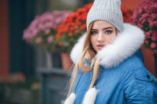 Zakochana w naturze dziewczyna w kurtce spaceruje po jesiennym parku.