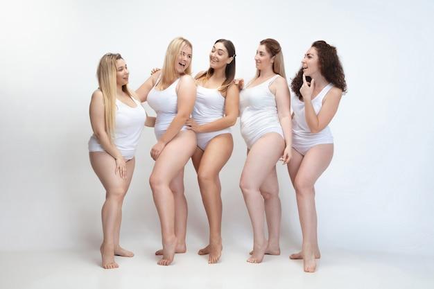 Zakochana w sobie. portret młodych kobiet piękny plus rozmiar pozowanie na biały