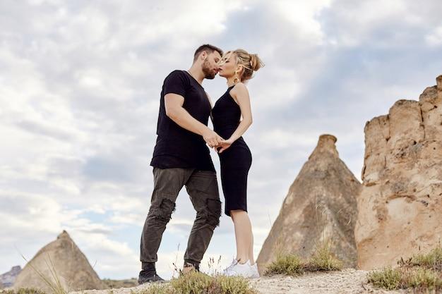Zakochana wschodnia para w górach kapadocji ściska i całuje. miłość i emocje kochająca para na wakacjach w turcji. portret mężczyzny i kobiety. piękne kolczyki półksiężyca na uszach dziewczynki