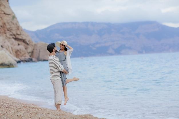 Zakochany mężczyzna i kobieta, ciesząc się razem blisko morza, biegając po plaży, śmiejąc się, całując