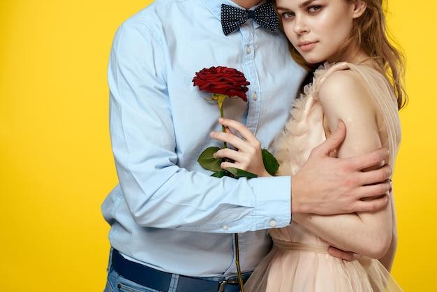 Zakochany mężczyzna i kobieta z czerwoną różą na białym tle