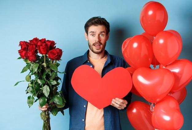 Zakochany mężczyzna przynosi niespodzianki na romantyczną randkę, trzymając bukiet czerwonych róż i walentynkowe czerwone serce, stojąc w pobliżu balonów i patrząc na kochanka, niebieskie tło.