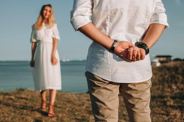 Zakochany młody mężczyzna przygotowuje się do złożenia swojej dziewczynie propozycji ślubu, chowając pierścionek za plecami.