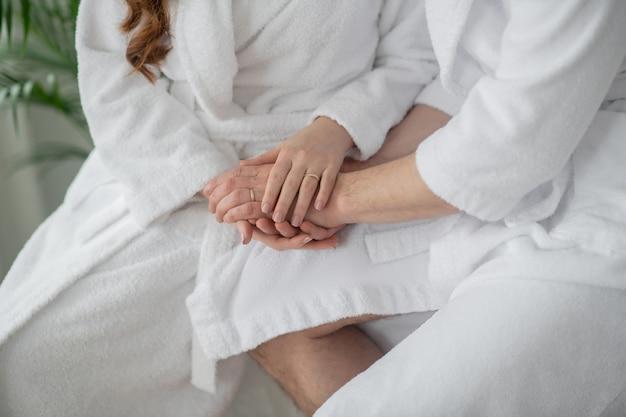 Zakochany. para w białych szlafrokach spędza razem czas i czuje się romantycznie