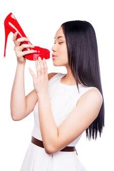 Zakochany w tych butach. piękna młoda azjatka w ładnej sukience całuje swoje nowe czerwone buty, stojąc na białym tle