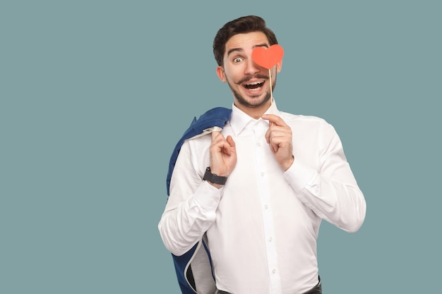 Zakochany zabawny mężczyzna w białej koszuli stojący i trzymający naklejkę z czerwonym sercem i patrzący w kamerę z zabawnymi otwartymi ustami i zdumioną twarzą i dużymi oczami. kryty, studio strzał na białym tle na jasnoniebieskim tle.