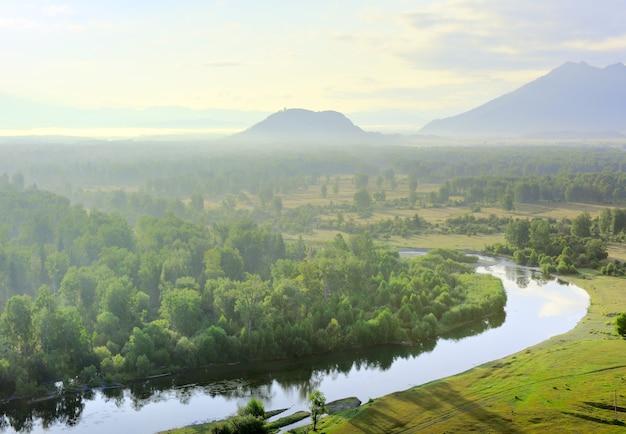 Zakole rzeki, wzgórza we mgle pod złotym niebem w górach ałtaju. syberia, rosja