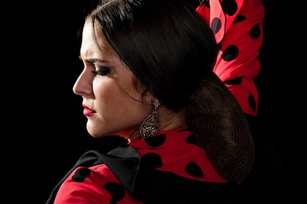 Zakończenia flamenca tancerz patrzeje w dół na czarnym tle