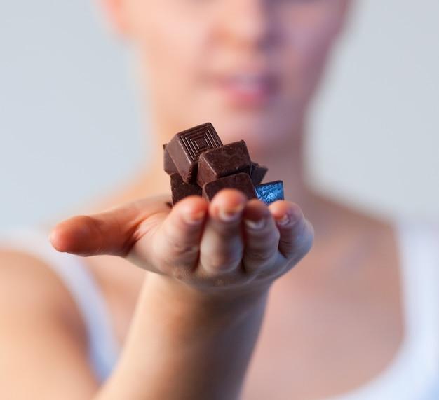 Zakończenie atrakcyjna kobieta trzyma czekoladową ostrość na czekoladzie