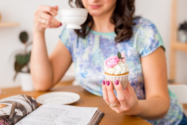 Zakończenie babeczka w ręce i filiżanka herbata. kobieta w kuchni pije godzinę z domowej roboty babeczką