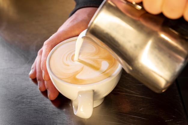 Zakończenie barista nalewa kawę w filiżankę