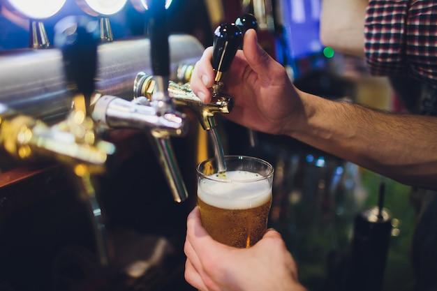 Zakończenie barmanu ręka przy piwa klepnięciem nalewa lanie piwo lager.