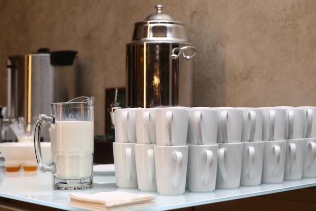 Zakończenie białe filiżanki i dzbanek mleko na lekkim stole