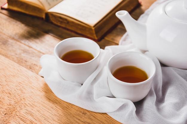 Zakończenie biały chiński herbaciany ustawiający na drewnianym stole