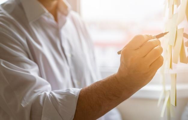 Zakończenie biznesmen bierze notatki przy biurem