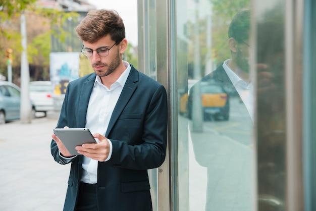 Zakończenie biznesmen opiera blisko szklanego drzwi używać cyfrową pastylkę