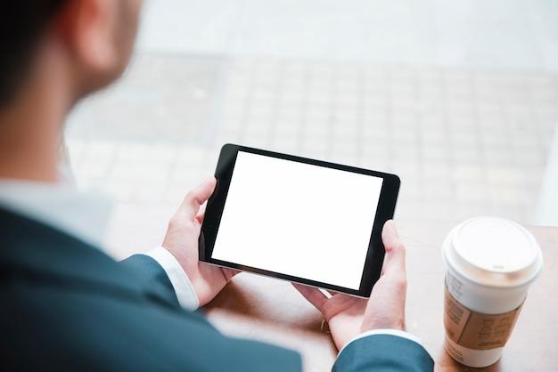 Zakończenie biznesmen patrzeje cyfrową pastylkę z białym ekranu pokazem w caf�