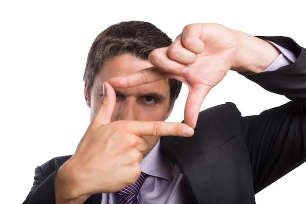 Zakończenie biznesmen patrzeje przez palec ramy