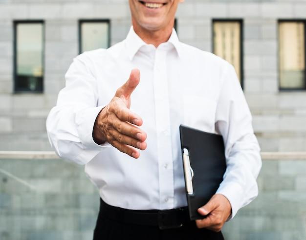 Zakończenie biznesmen trzyma out rękę