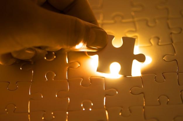 Zakończenie biznesmen up wręcza złączonego łamigłówka element i robi wyrzynarki zupełnym