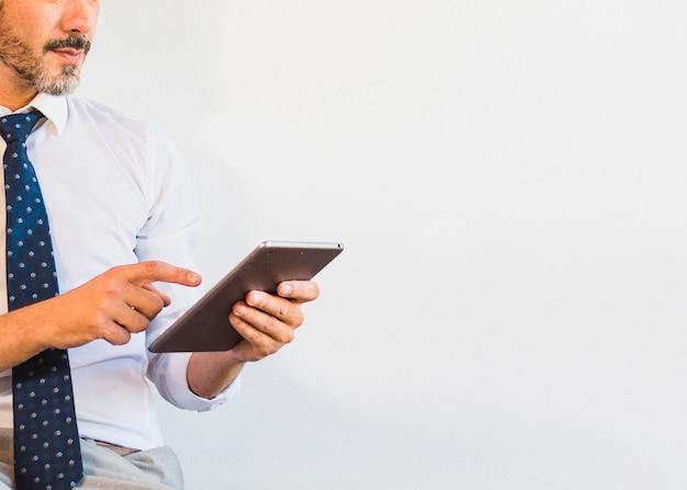 Zakończenie biznesmen używa cyfrową pastylkę przeciw białemu tłu