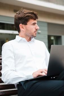 Zakończenie biznesmen używa na laptopie patrzeje daleko od