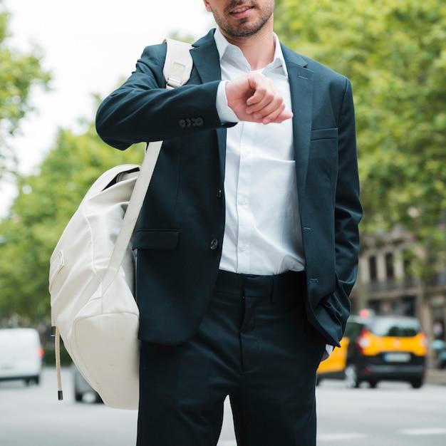Zakończenie biznesmen z białym plecakiem na jego ramieniu ogląda czas na ulicie