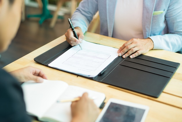 Zakończenie biznesmena obsiadanie przy stołowym i plombowanie w dokumencie