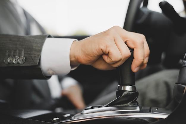 Zakończenie biznesmena ręka chwyta przekładnię w samochodzie