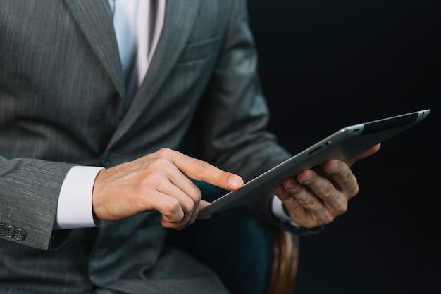 Zakończenie biznesmena ręka dotyka cyfrowego pastylka ekran