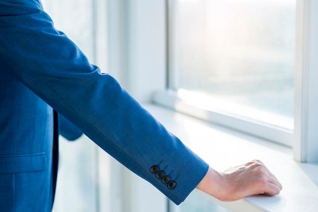 Zakończenie biznesmena ręka na windowsill