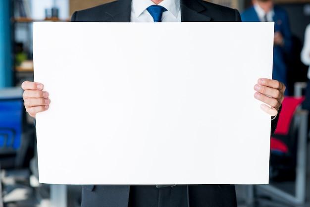 Zakończenie biznesmena ręka trzyma pustego białego plakat