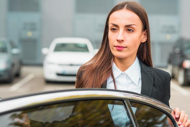 Zakończenie bizneswoman pozycja za samochodowym drzwi