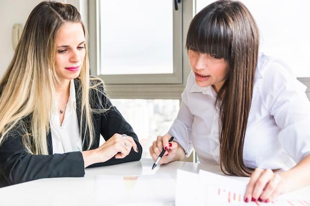 Zakończenie bizneswomany analizuje biznesowego raport w biurze