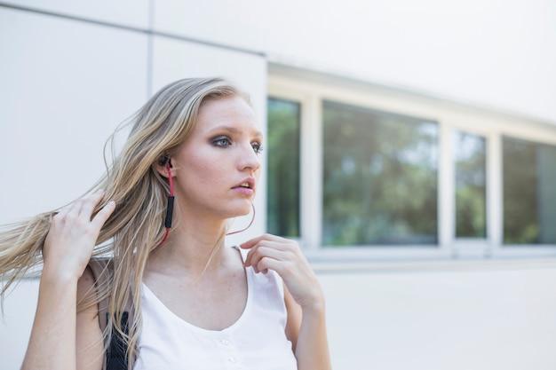 Zakończenie blondynki młodej kobiety słuchająca muzyka na słuchawce