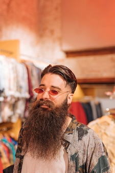 Zakończenie brodaty młody człowiek jest ubranym okulary przeciwsłonecznych stoi w sklepie odzieżowym