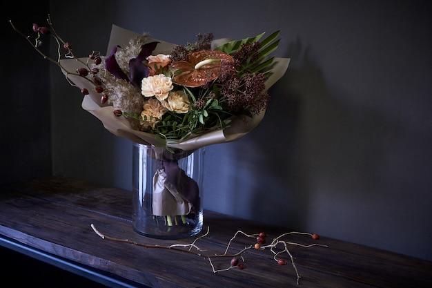 Zakończenie bukiet w szklanej wazie dekorującej w rocznika stylu na ciemnym tle