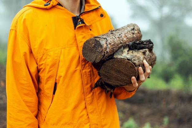 Zakończenie caucasian mężczyzna mienia łupka up notuje dalej mgłowego las jest ubranym pomarańczowego deszczowiec podczas deszczowego dnia