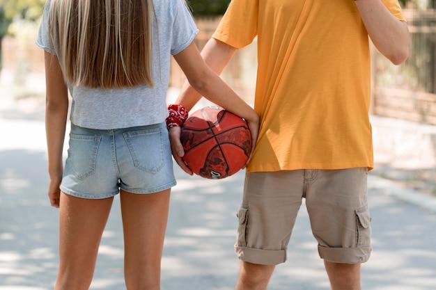 Zakończenie chłopiec i dziewczynka trzymając piłkę
