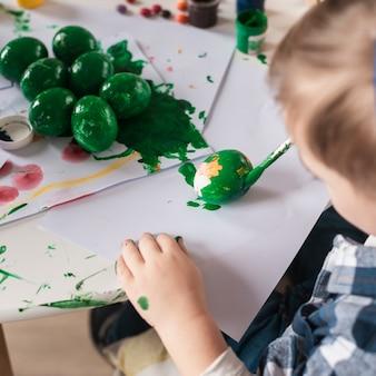 Zakończenie chłopiec maluje tradycyjnych jajka dla easter