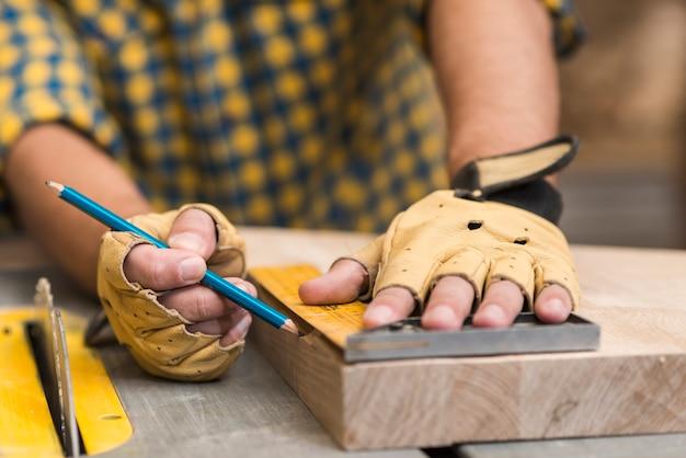 Zakończenie cieśla mierzy drewnianego blok używać władcy na stole roboczym