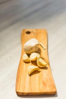 Zakończenie czosnków cloves na drewnianej ciapanie desce
