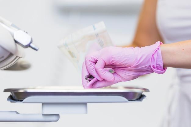 Zakończenie dentysty ręka trzyma stomatologicznych narzędzia