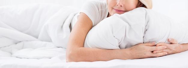 Zakończenie dojrzała kobieta trzyma poduszkę