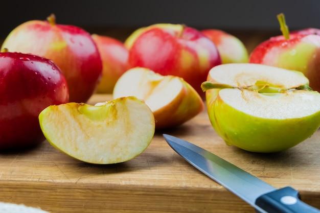 Zakończenie dojrzali soczyści jabłka na drewnianym stole. krajowi organicznie jabłka i nóż na wieśniaka stołu stole