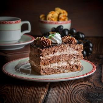Zakończenie domowej roboty tort z filiżanką herbata, ciastka i jagody na drewnianym stole