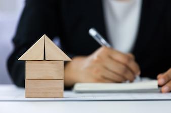 Zakończenie domowy architektoniczny model z biznesmenów znaków kontraktem za plamy tłem