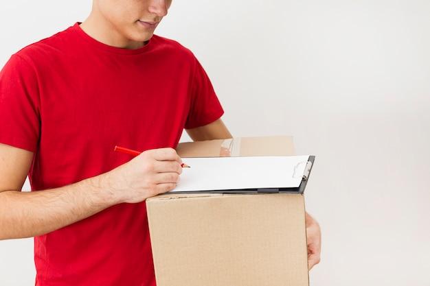 Zakończenie doręczeniowy mężczyzna podpisuje dla dostawy paczki