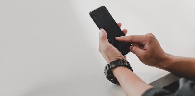 Zakończenie dotyka jego smartphone w biurowym pokoju młody biznesmen